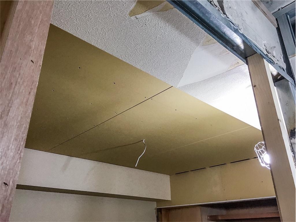 ボードが貼られたWICと洋室の天井
