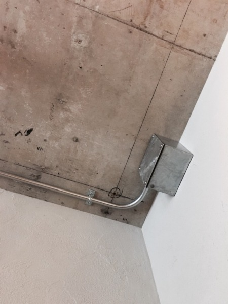 無機質な配管ボックスとコンクリート天井